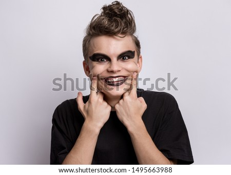 Portrait of crazy teen boy with spooking make-up on grey background. Young teenager in style of punk goth dressed in black looking at camera with big smile. Problems of transitional age.