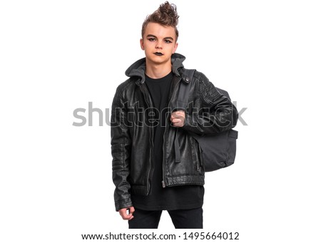 Portrait of teen boy student with spooking make-up holds bag, isolated on white background. Teenager with backpack in style of punk goth dressed in black. Problems of transitional age.