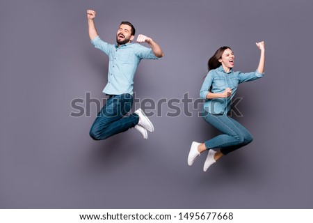 Full size photo of delighted students jump raise fists scream yeah celebrate victory wear denim jeans isolated over gray background #1495677668