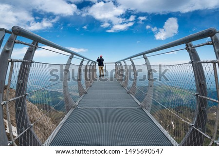 A man observes the imposing landscape on a walkway that looks into the air at the Pic du Midi in Bigorre, in the Pyrenees Mountains (France).