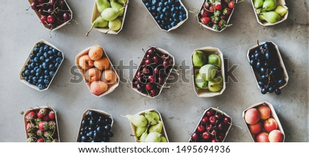 Summer fruit, berry assortment. Flat-lay of strawberries, cherries, grape, blueberries, pear, apricot, fig in eco-friendly boxes over grey background, top view, wide composition. Local farmers produce #1495694936