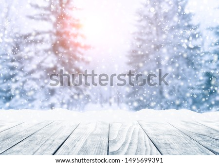 Wooden table top on winter sunny landscape with fir trees. Merry Christmas and happy New Year greeting background. Winter landscape with snow and christmas trees.  #1495699391