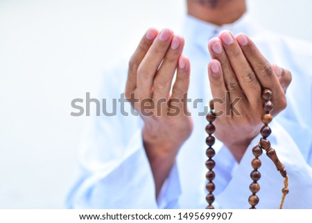 Muslim man in white session lift two hand for praying ,isolated on white background.concept for Ramadan, Eid al Fitr, eid ad-ha, meditation, islamic praying Royalty-Free Stock Photo #1495699907