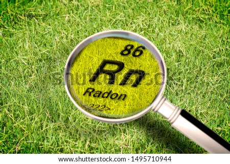 The dangerous radioactive radon gas under the ground - concept image with periodic table of the elements, magnifying lens and green grass area on background. #1495710944