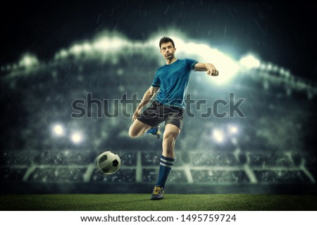 Soccer player in action on a dark background #1495759724