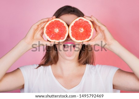 Playful young woman holding juicy halves of grapefruit, citrus fruits against her eyes and making funny face with tongue out. Diet concept  #1495792469
