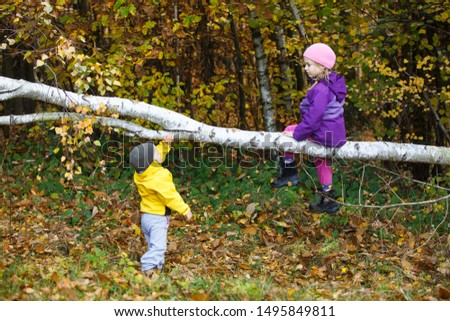 Brother and sister playing in autumn woods  #1495849811