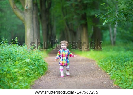 Cute baby girl in rubber rain boots walking in a rainy park #149589296