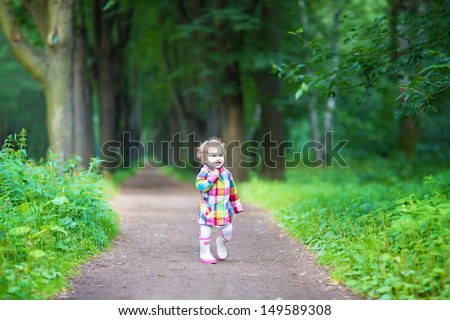 Funny curly baby girl in rain boots walking in a park #149589308