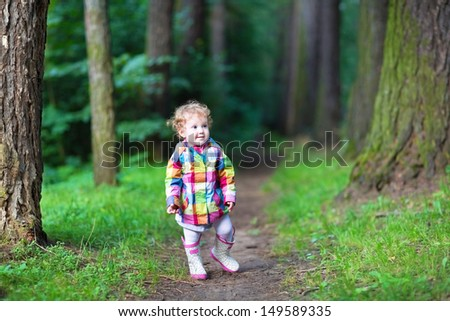 Sweet baby girl in a rain jacket and boots walking in an autumn park #149589335