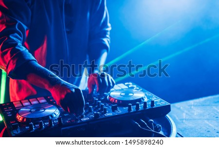 Dj mixes the track in the nightclub at a party, Christmas, new year Royalty-Free Stock Photo #1495898240