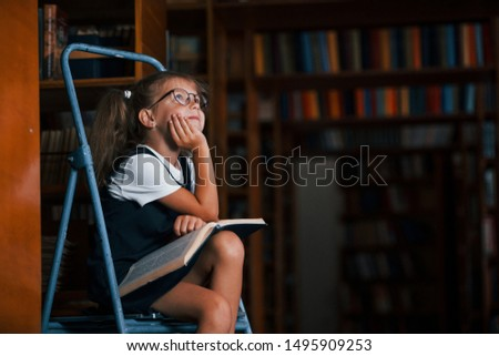 Thoughtful look. School girl on the ladder in library full of books. Education conception.