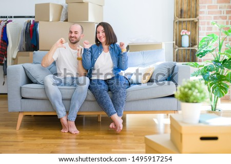 Young couple sitting on the sofa arround cardboard boxes moving to a new house looking confident with smile on face, pointing oneself with fingers proud and happy. #1495917254