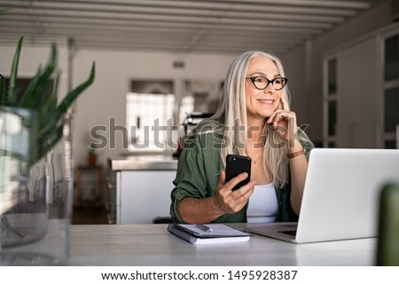 Happy senior woman holding smartphone and laptop daydreaming while looking away. Successful stylish old woman working at home while thinking. Fashionable lady entrepreneur wearing cool eyeglasses. #1495928387