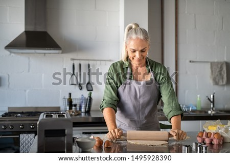 Happy senior woman preparing christmas cookies at home. Mature woman rolling dough for biscuits on kitchen counter. Old lady wearing apron rolling pastry with wooden rolling pin and smiling. #1495928390