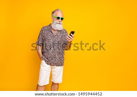 Portrait of funny funky old bearded man in green eyeglasses eyewear use his cell phone to find route on journey read news  wearing shorts leopard print shirt isolated over yellow background #1495944452