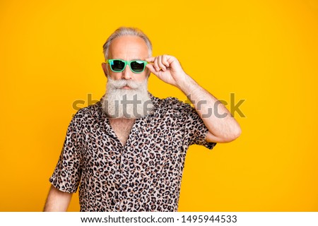 Photo of serious confident old man holding his glasses staring into camera while isolated with yellow background #1495944533