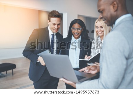 Diverse group of smiling businesspeople discussing work over a laptop while standing together in a bright modern office #1495957673
