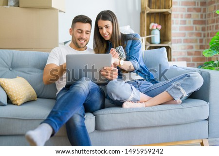 Young couple moving to a new home relaxing sitting on the sofa using computer laptop, smiling happy for moving to new apartment #1495959242