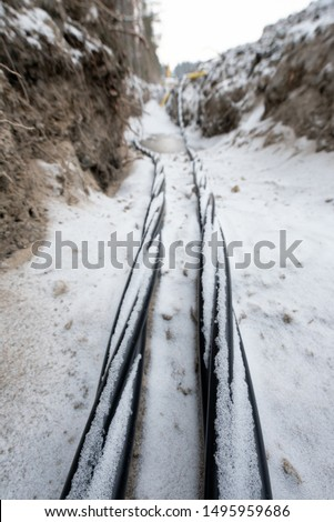 Laying a fiber optic and electricity cables in the frozen ground, buried cables for fast internet in rural region - underground cabling in Finland #1495959686