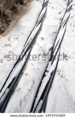 Laying a fiber optic and electricity cables in the frozen ground, buried cables for fast internet in rural region - underground cabling in Finland #1495959689