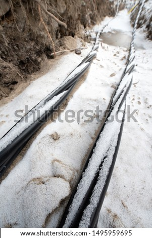 Laying a fiber optic and electricity cables in the frozen ground, buried cables for fast internet in rural region - underground cabling in Finland #1495959695