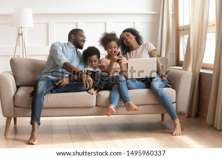 African mother using pc pre-teen daughter having fun online holds smartphone toddler son enjoy tablet computer activity father in glasses hold in hand cell phone, family addicted with gadgets concept