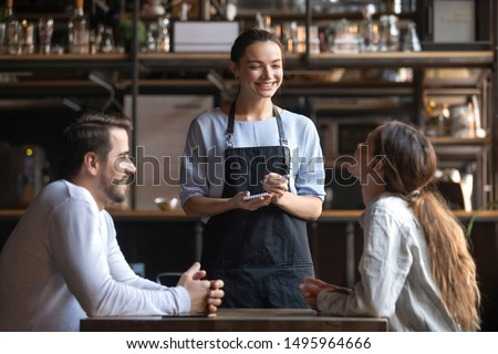 Smiling waitress wear apron hold notepad pen take order talk to clients serving restaurant guests couple choosing food drinks menu sit at cafe coffeehouse table, waiting staff, good customer service #1495964666