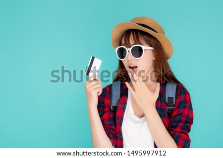 Beautiful young asian woman wear hat and sunglasses with showing and surprise with credit card to travel summer trip isolated on blue background, girl journey in vacation with payment finance on card. #1495997912