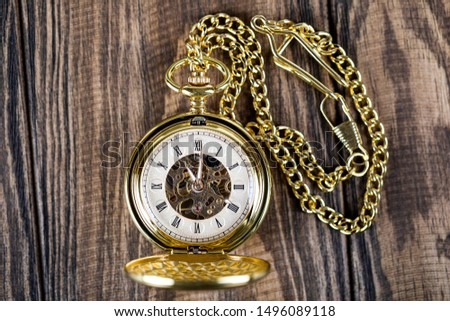 Vintage pocket watch on a chain lie on a wooden table. Roman numerals on the dial. #1496089118