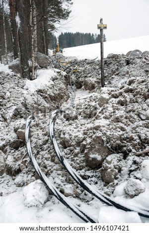 Laying a fiber optic and electricity cables in the frozen ground, buried cables for fast internet in rural region - underground cabling in Finland #1496107421