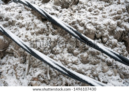 Laying a fiber optic and electricity cables in the frozen ground, buried cables for fast internet in rural region - underground cabling in Finland #1496107430