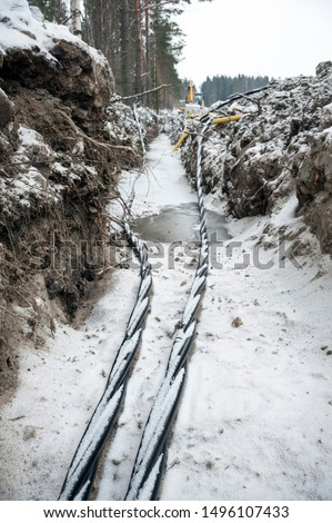 Laying a fiber optic and electricity cables in the frozen ground, buried cables for fast internet in rural region - underground cabling in Finland #1496107433