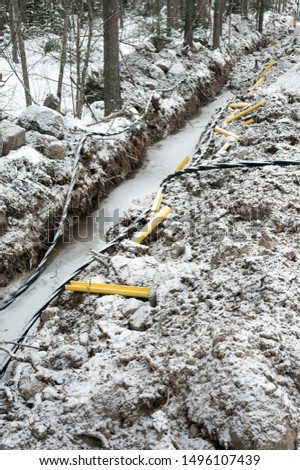 Laying a fiber optic and electricity cables in the frozen ground, buried cables for fast internet in rural region - underground cabling in Finland #1496107439