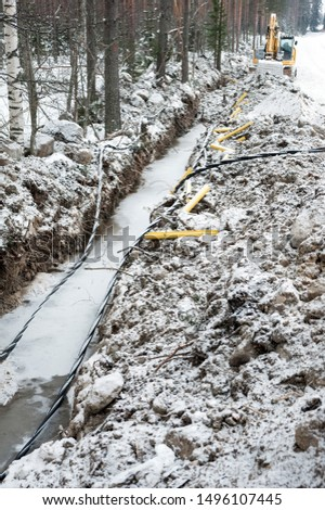Laying a fiber optic and electricity cables in the frozen ground, buried cables for fast internet in rural region - underground cabling in Finland #1496107445