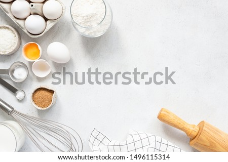 Cooking And Baking Ingredients Utensils On White Concrete Background. Kitchen Food Frame. Eggs Sugar Milk Whisker Rolling Pin And Measuring Spoons With Spices #1496115314