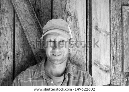 Black and White image of an average man with a ball cap and plaid shirt. Royalty-Free Stock Photo #149622602