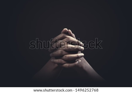 Praying hands with faith in religion and belief in God on dark background. Power of hope or love and devotion. Royalty-Free Stock Photo #1496252768