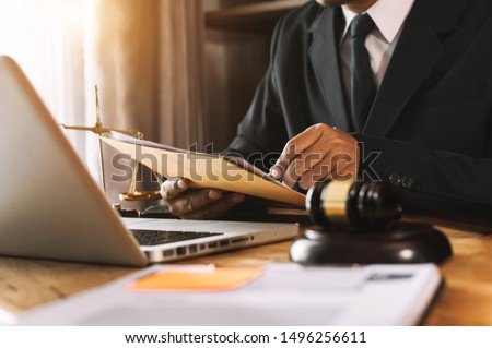 Justice and law concept.Male judge in a courtroom with the gavel, working with, computer and  docking keyboard, eyeglasses, on table in morning light  #1496256611