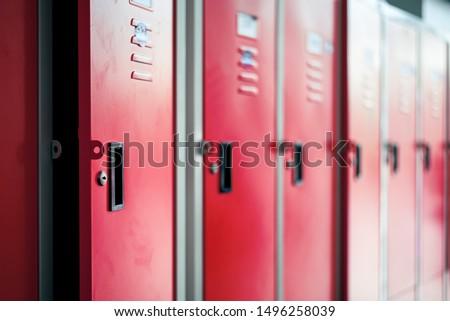 Row of red metal lockers in locker room Royalty-Free Stock Photo #1496258039