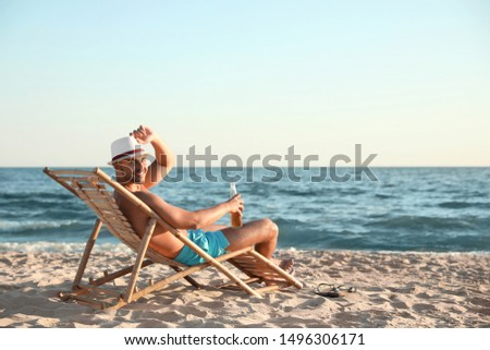 Young man relaxing in deck chair on beach near sea #1496306171