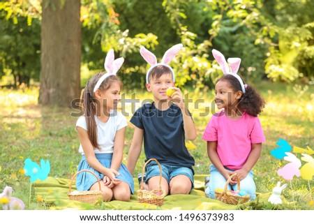 Little children gathering Easter eggs in park #1496373983