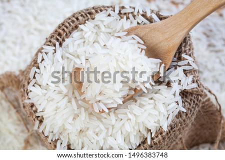 Close up the rice on wood spoon put on the rice sack with blurry of pile rice #1496383748