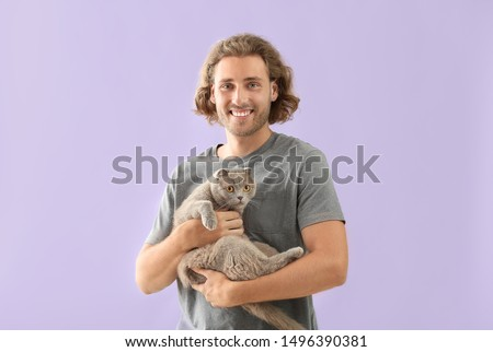 Man with cute funny cat on color background