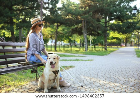 Young blind woman with guide dog in park #1496402357