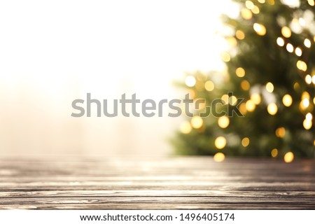 Empty table and blurred fir tree with yellow Christmas lights on background, bokeh effect. Space for design #1496405174