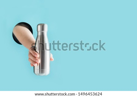 Reusable metal bottle for drinks in female hand through the hole in paper. Individual use. Save the planet. Zero waste concept. Plastic free. #1496453624