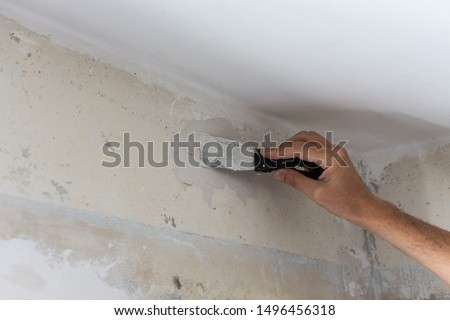 The worker covers the uneven walls, man's hands with a spatula and putty, apartment repair #1496456318