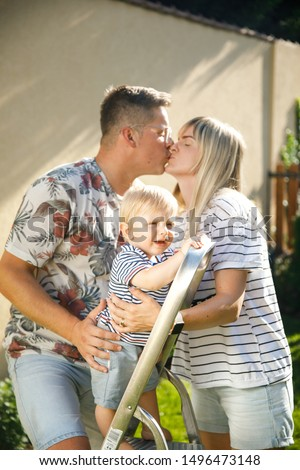 Happy family outdoor. mom, son and dad on the back yard. happy parenting concept. family splash on each other water from the hose. maternity leave. toddler boy. blond family. young family photo shoot. #1496473148