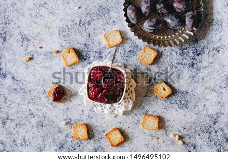 homemade plum jam and fresh plums on a blue background #1496495102
